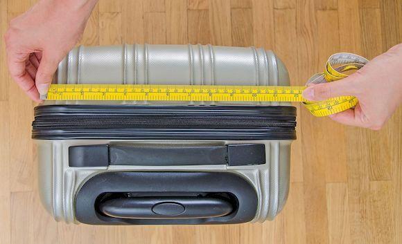 Измерение чемодана рулеткой