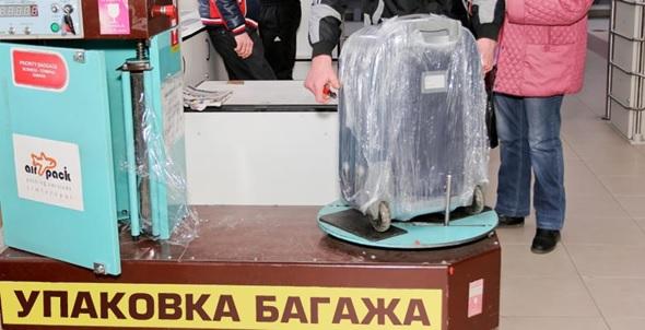 Упаковка чемодана в пленку в аэропорту