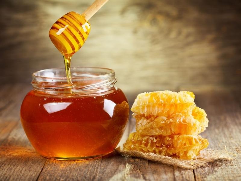 Банка с медом и рядом соты