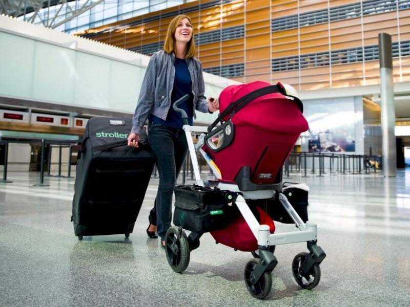 Женщина с коляской и багажом для самолета