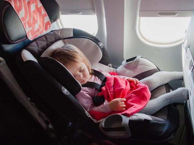 Ребенок спит в люльке в самолете