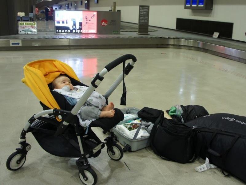 Ребенок в коляске и рядом чемодан с вещами